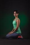 运动的妇女,健身妇女坐与绿色背后照明的黑暗的背景 免版税库存图片