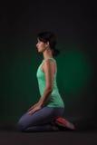 运动的妇女,健身妇女坐与绿色背后照明的黑暗的背景 图库摄影