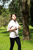 运动的妇女锻炼,当听音乐使用移动电话a时 免版税库存图片