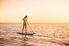 运动的少妇站立冲浪与美好的日落或日出颜色的桨 免版税库存照片