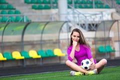 运动的性感的妇女保留在腿之间的橄榄球球 免版税库存图片