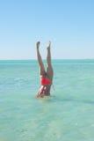 运动的比基尼泳装妇女手倒立海洋水 图库摄影