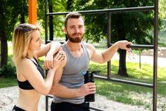 运动的白肤金发的休息在锻炼trainin以后的女孩和有胡子的人 免版税库存照片