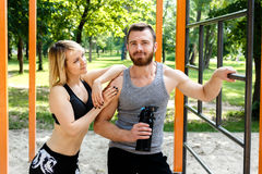 运动的白肤金发的休息在锻炼trainin以后的女孩和有胡子的人 免版税库存图片