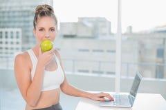 运动的白肤金发的吃苹果,当使用膝上型计算机时 免版税图库摄影