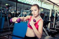 年轻运动的白肤金发的妇女做与重量的体育运动在健身房 免版税库存照片