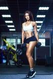 运动的短裤和顶面举行的哑铃的年轻适合的妇女,当站立在健身房时 免版税库存照片