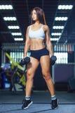 运动的短裤和顶面举行的哑铃的年轻适合的妇女,当站立在健身房时 库存照片