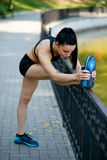 运动的美丽的在腿的年轻女人实践的舒展锻炼,解决,佩带的运动服 免版税库存照片