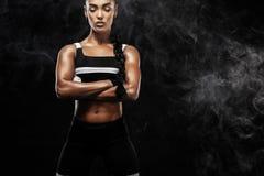运动的美好的美国黑人的模型, sportwear的妇女做健身行使在黑背景的停留适合 免版税库存照片