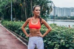 运动的适合式样身分全长画象在摆在桃红色的公园炫耀胸罩和白色绑腿用手  免版税库存图片