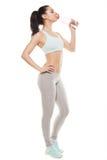运动的从一个瓶的女孩饮用水在锻炼以后,健身 库存照片