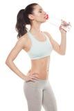 运动的从一个瓶的女孩饮用水在锻炼以后,健身 免版税图库摄影