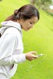 运动的从她的智能手机的妇女听的音乐 库存图片