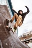 运动衫和牛仔裤的一位少年溜冰者在skatepark的一个滑板乘坐墙壁, 免版税库存图片