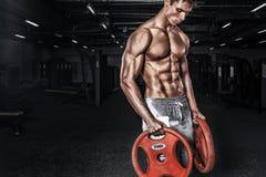 运动赤裸上身的年轻体育人-健身模型拿着在健身房的杠铃 复制空间前面您的文本 库存图片