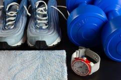 运动鞋、哑铃、一块毛巾和一块手表在黑暗的背景 免版税图库摄影