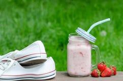 运动鞋、在绿草,拷贝空间背景的杯子酸奶和草莓  库存图片