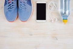 运动鞋、智能手机和水在木头与在底层copyspace 库存照片