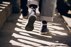 运动鞋和方格花纹裤的一个人走在路面的 免版税库存照片