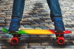 运动鞋和牛仔裤的一个年轻溜冰板者,站立在他的冰鞋 滑板和脚的特写镜头片段 库存照片