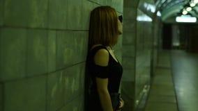 运动鞋和玻璃的美丽的时尚女孩在地下过道站立 影视素材