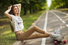 运动鞋和T恤杉裤子的女孩在他的顶头生活方式画象后投入了longboard腿和手 库存图片