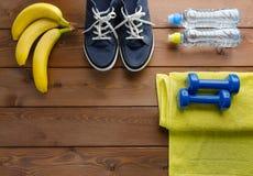 运动鞋哑铃水毛巾和瓶在木桌上的 库存图片