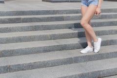 运动鞋的美丽的长,苗条腿女孩和牛仔布短裤在楼梯夏日 图库摄影