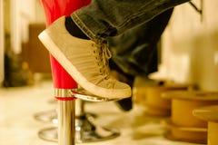 运动鞋鞋子在老椅子的腿逗留 库存照片