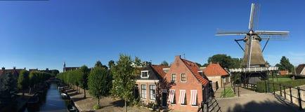 从运河、房子和一台老风车的全景 库存图片