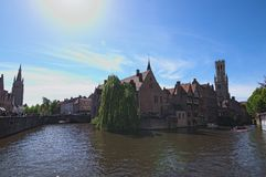 运河在布鲁日和著名钟楼在背景耸立在一个美好的春日 免版税库存照片