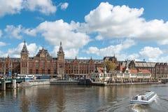 运河在阿姆斯特丹中央火车站前面的巡航小船 库存照片
