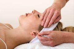 运用耳朵针灸技术的按摩医生。 免版税库存图片