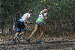运行上升在森林的两个运动员赛跑者 免版税库存照片