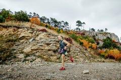 运行与在一个山行迹的拐杖的运动员赛跑者在秋天风景 免版税库存照片