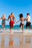 运行假期的海滩朋友 免版税图库摄影