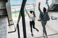 运行到体育场的运动服的两个愉快的女运动员 库存照片