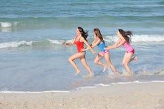 运行十几岁假期的海滩孩子 免版税库存照片