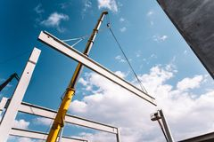 运行和运转在建造场所移动的水泥射线和柱子的工业起重机 免版税库存图片