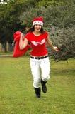 运行圣诞老人的女孩 免版税库存图片