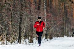 运行在一串多雪的足迹的公赛跑者在杉木森林里 免版税库存照片