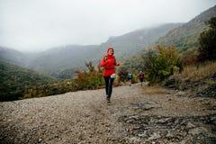 运行在一件红色夹克的雨中的女孩赛跑者有在面孔的微笑的 库存照片