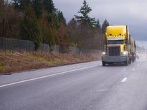 运行在下雨的高速公路的黄色经典大半船具卡车 库存图片