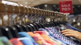 运行在与五颜六色的精神衬衣的挂衣架的女性手 寻找男朋友的少妇礼物在衣物商店 影视素材