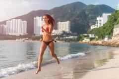 运行在与发光秘密审议和旅馆手段小山的太阳的海滩的适合的女运动员佩带的比基尼泳装在背景中 免版税图库摄影
