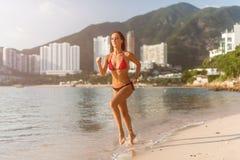 运行在与发光秘密审议和旅馆手段小山的太阳的海滩的适合的女运动员佩带的比基尼泳装在背景中 库存照片