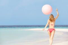 运行在与气球的美丽的海滩的比基尼泳装的妇女 免版税库存图片