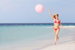 运行在与气球的美丽的海滩的比基尼泳装的妇女 库存图片