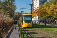 运行在与秋季树的火车站附近的黄色电车轨道 库存照片